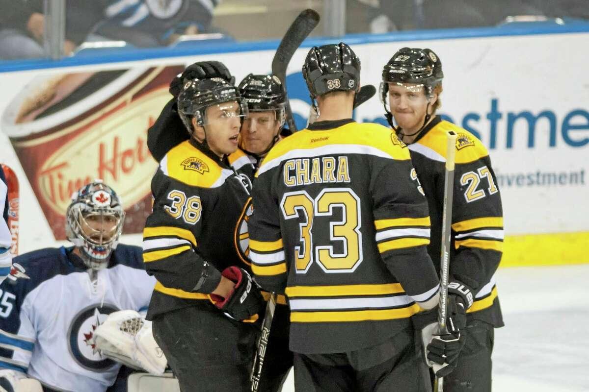 The Boston Bruins celebrate a goal in front of Winnipeg Jets goalie Al Montoya during the second period of a preseason game Friday in Saskatoon, Saskatchewan.