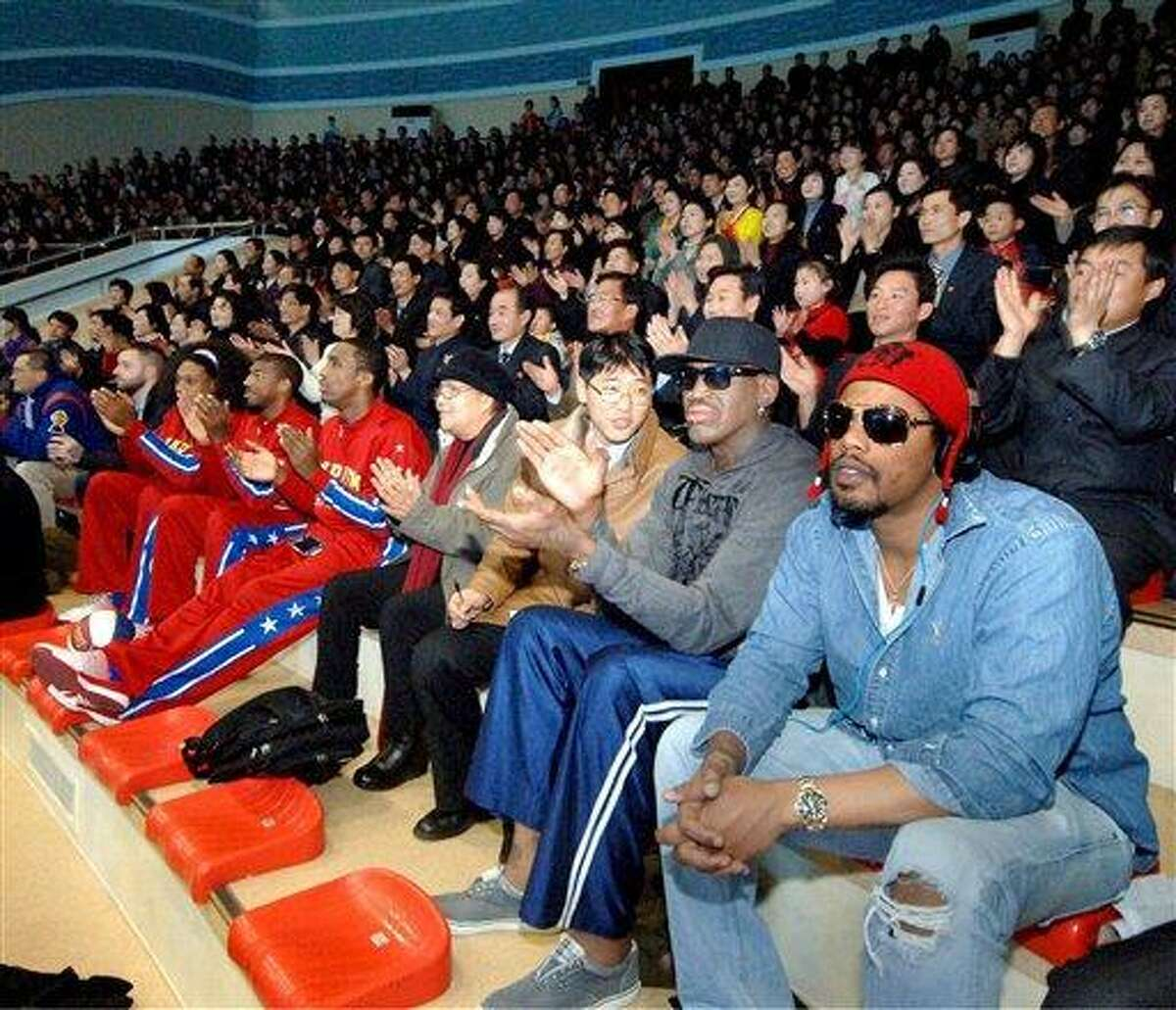"""In this image released by the Korean Central News Agency (KCNA) and distributed by the Korea News Service, former NBA star Dennis Rodman, second right in front row, visits a dolphin aquarium in Pyongyang in North Korea Friday, March 1, 2013. Ending his unexpected round of basketball diplomacy in North Korea on Friday, Rodman called leader Kim Jong Un an """"awesome guy"""" and said his father and grandfather were """"great leaders."""" AP Photo/KCNA"""