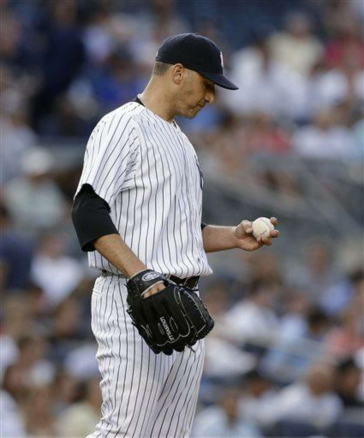 New York Yankees starting pitcher Andy Pettitte looks at the ball after allowing four runs to the Texas Rangers in the third inning of a baseball game, Wednesday, June 26, 2013, in New York. (AP Photo/Kathy Willens)