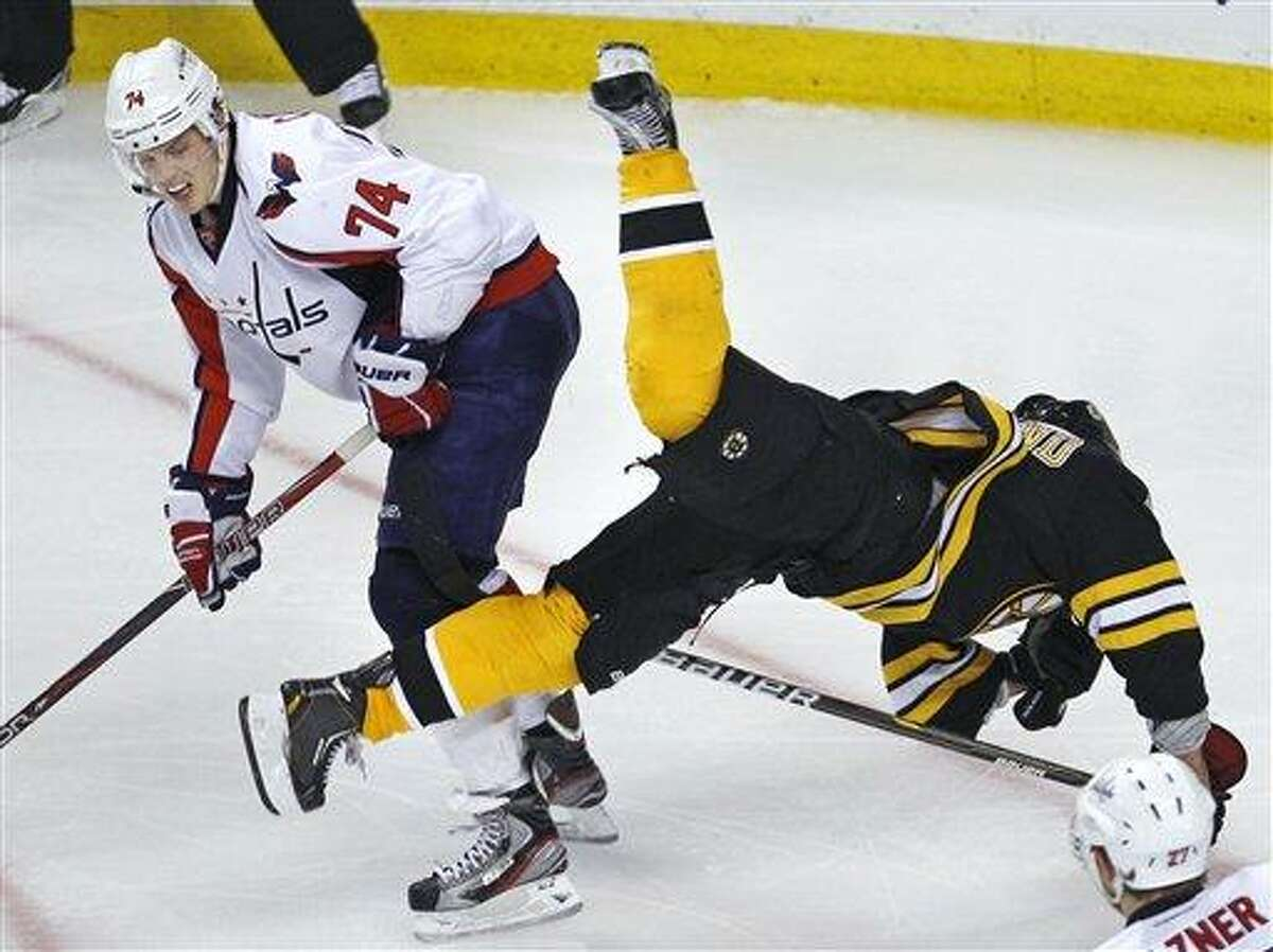 Washington Capitals defenseman John Carlson (74) upends Boston Bruins left wing Brad Marchand (63) during the third period of Game 1 of an NHL hockey Stanley Cup first-round playoff series in Boston, Thursday, April 12, 2012. (AP Photo/Charles Krupa)