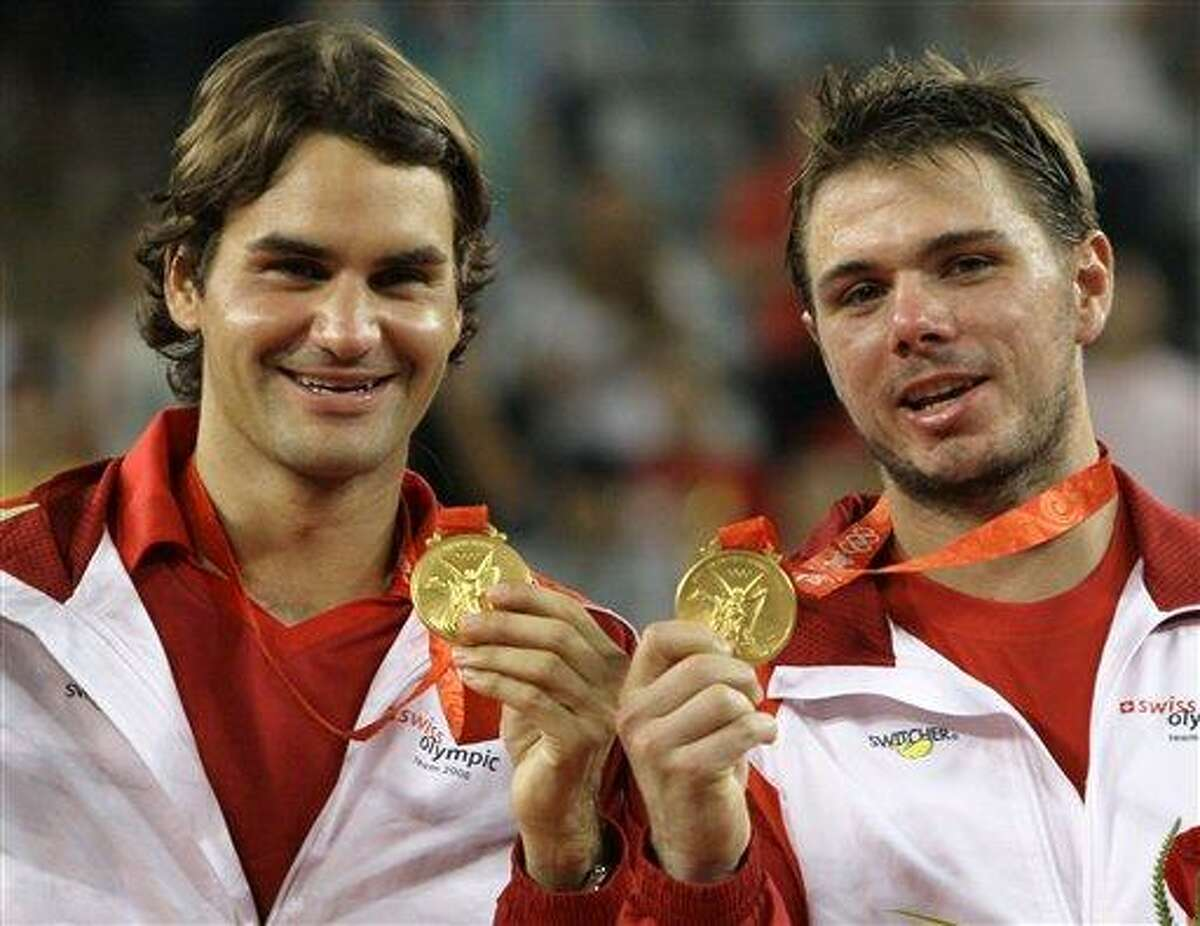 FILE- In this Saturday, Aug. 16, 2008, file photo, Roger Federer, left, and Stanislas Wawrinka of Switzerland celebrate winning the men's tennis doubles gold medal at the Beijing 2008 Olympics in Beijing. Roger Federer passed on carrying Switzerland's flag at his third straight Summer Olympics opening ceremony this week, so Wawrinka can have the honor in London on Friday, July 27, 2012 (AP Photo/Elise Amendola, File)