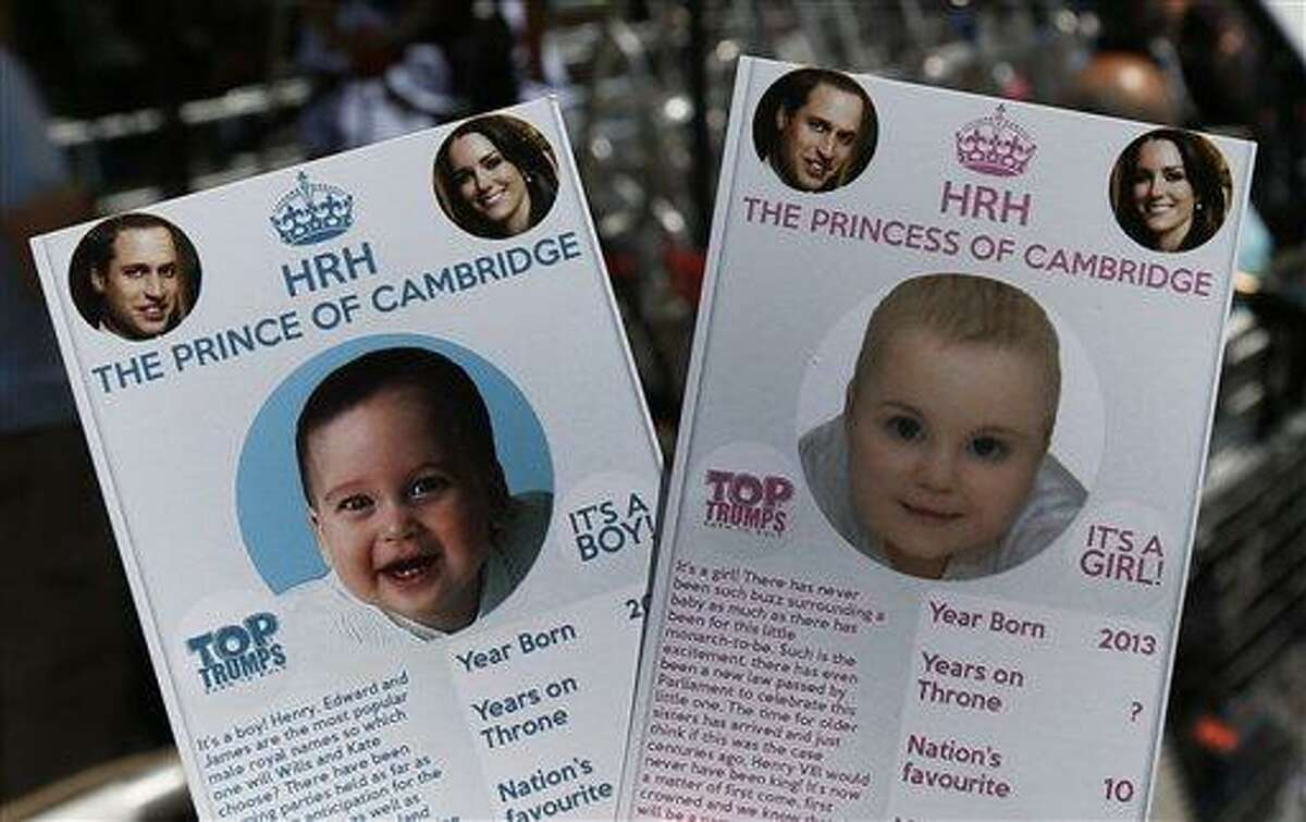 Cards depicting the 'royal baby' either as a boy or a girl, specially made by a games company as a publicity stunt, are pictured here, backdropped by members of the media waiting across from the St. Mary's Hospital exclusive Lindo Wing in London, Thursday, July 11, 2013. Media are preparing for royal-mania as Britain's Duchess of Cambridge plans to give birth to the new third-in-line to the throne in mid-July, at the Lindo Wing. Cameras from all over the world are set to be jostling outside for an exclusive first glimpse of Britain's Prince William and the Duchess of Cambridge's first child. (AP Photo/Lefteris Pitarakis)