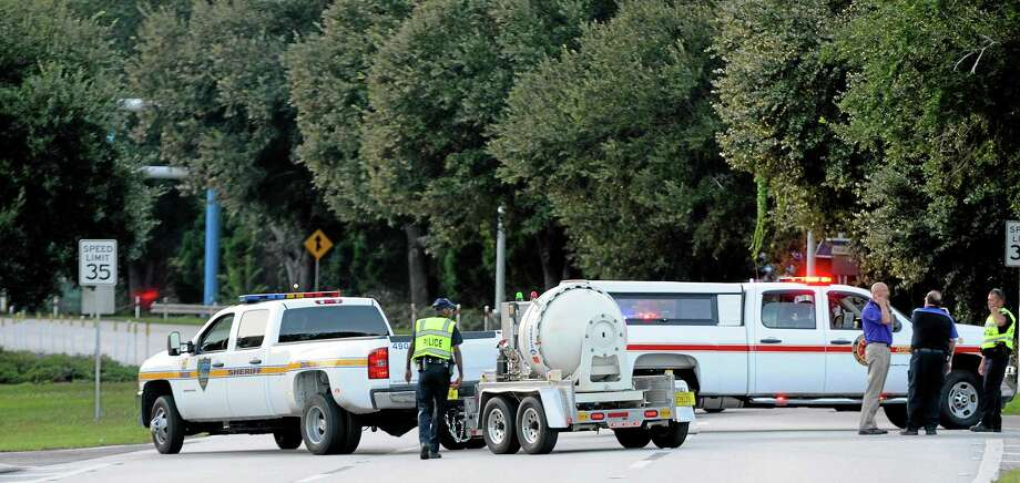 Police block the road to the Jacksonville International Airport terminal as the bomb disposal unit drives by on the right Tuesday, Oct. 1, 2013, in Jacksonville, Fla. The airport was evacuated after authorities found two suspicious packages. (AP Photo/The Florida Times-Union, Bruce Lipsky) Photo: AP / The Florida Times-Union