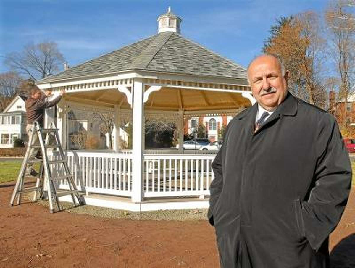 Cromwell Police Chief Anthony Salvatore stands in front of the gazebo installed on the Veterans Green in Cromwell. The gazebo was purchased from Klotter Farms in Ellington and donated by the Travelers Championship. In the background is Klotter Farms carpenter Kevin Plourde. Catherine Avalone/The Middletown Press