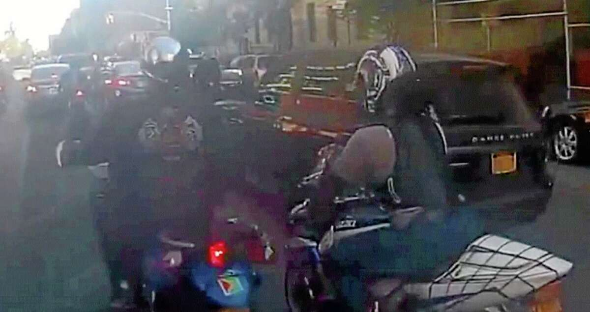 In this frame grab from video provided by the New York Police Department, motorcyclists ride alongside a sport utility vehicle, Sunday, Sept. 29, 2013, in New York. Police say that a man driving with his family along a New York City highway was attacked and beaten by a large group of motorcyclists who first surrounded his sport utility vehicle and stopped it on the road, then chased him for miles after he plowed through the blockade of bikes in an attempt to escape. (AP Photo/New York Police Department)