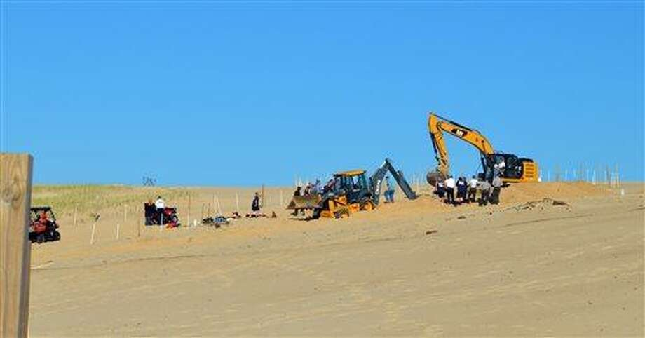 In this Friday, June 12, 2013, photo, Michigan City firefighters, police, and first responders dig through a sand dune at Mount Baldy near Michigan City, Ind., while searching for a missing 6-year-old-boy who fell into a hole. Lakeshore Ranger Bruce Rowe said it took crews using heavy excavating equipment about 3.5 hours to pull the boy out, saying he was buried under 11 feet of sand at a dune known as Mount Baldy. The boy initially was taken to Franciscan St. Anthony Health Medical Center, then flown to a Chicago hospital. (AP Photo/The News Dispatch, Julie McClure) Photo: AP / Michigan City News Dispatch