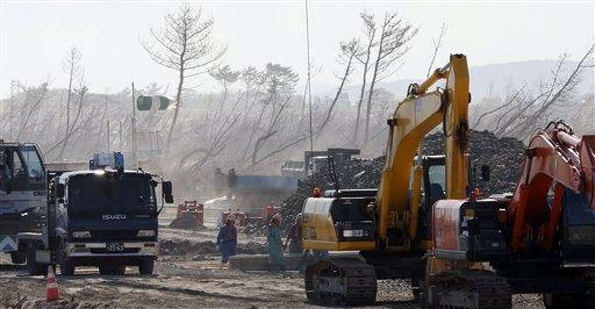 In this Oct. 9, 2012 photo, with a backdrop of leaning pine trees, part of windbreak forests severely damaged by the March 11, 2011 earthquake and tsunami, construction works continue near the Arahama Beach in Sendai, northeastern Japan. Japan's government has suspended 35 projects included in a budget for reconstruction from the disasters after criticism the spending was not directly related to recovery from them. As much as a fourth of the 11.7 trillion yen ($148 billion) budget had been earmarked for unrelated projects, including subsidies for a contact lens factory in another region and research whaling. However, the 35 projects put on hold during a meeting chaired by Prime Minister Yoshihiko Noda involved spending of only 16.8 billion yen ($210 million). (AP Photo/Koji Sasahara, File)