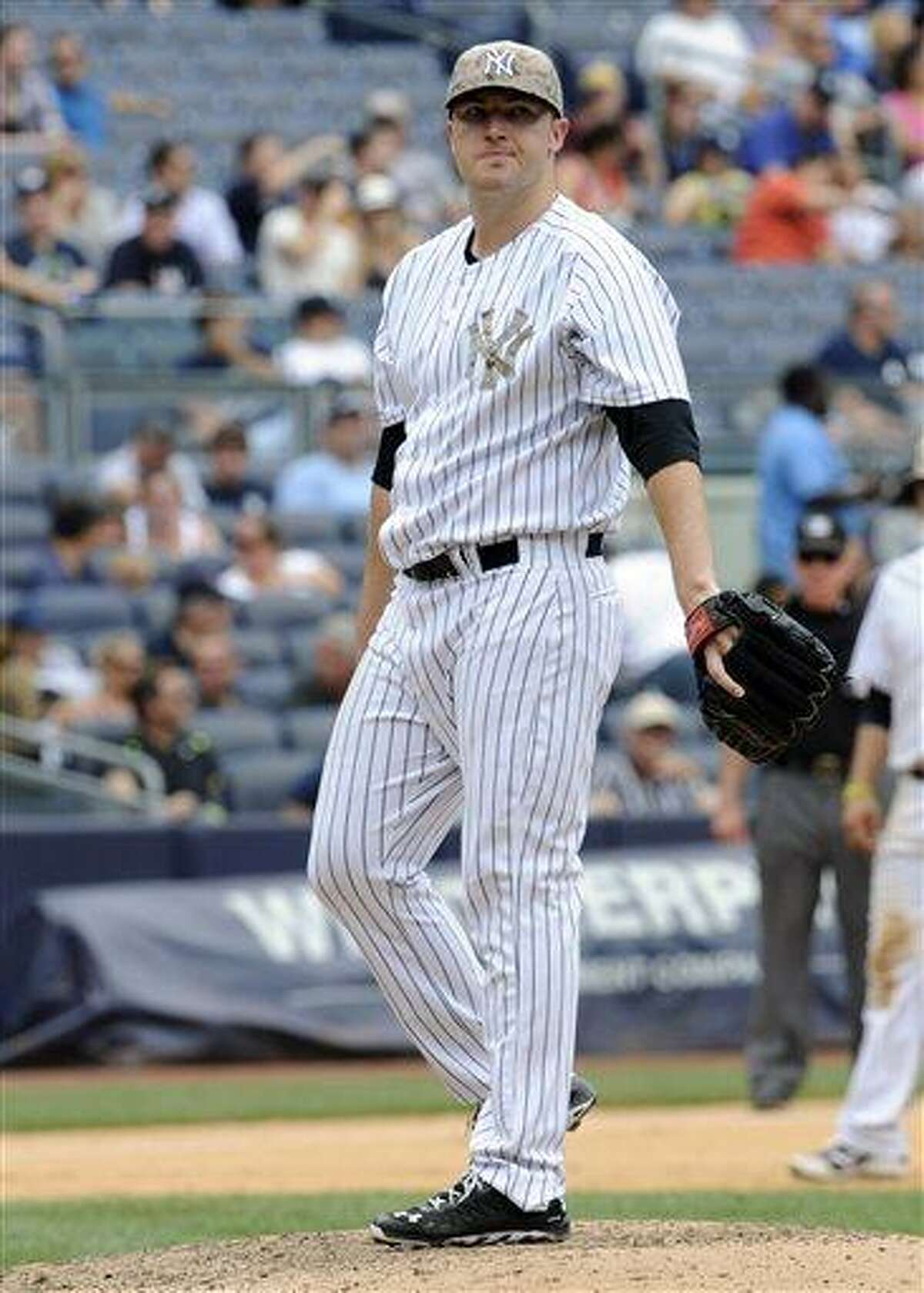 New York Yankees pitcher Phil Hughes reacts as manager Joe Girardi heads to the mound to take him out of the baseball game during the eighth inning after he gave up a two-run home run to Minnesota Twins' Pedro Florimon Saturday, July 13, 2013, at Yankee Stadium in New York. (AP Photo/Bill Kostroun)