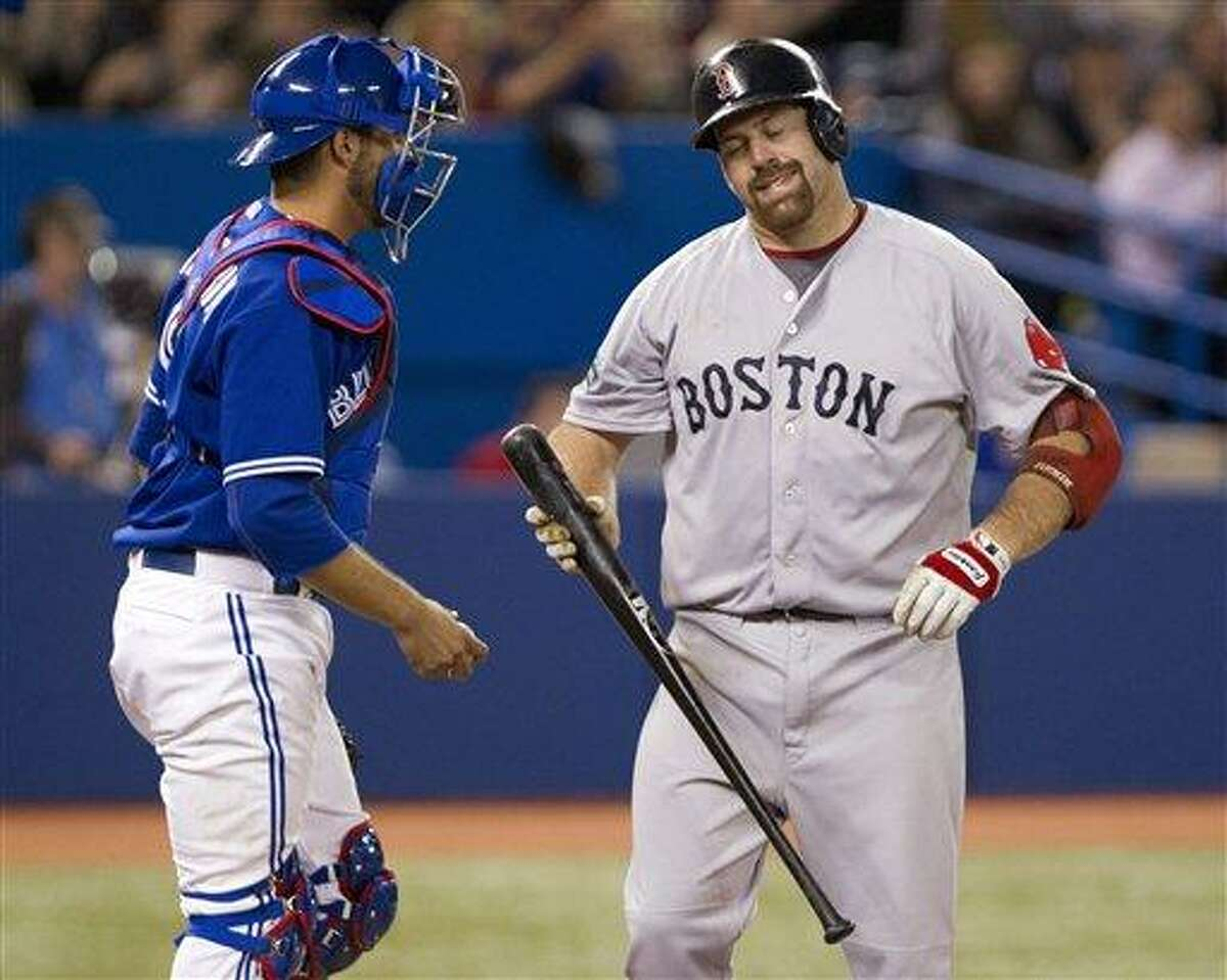 Boston Red Sox Kevin Youkilis, right, reacts in front of Toronto Blue Jays catcher J.P. Arencibia after striking out during ninth inning of a baseball game in Toronto on Wednesday, April 11, 2012. (AP Photo/The Canadian Press, Frank Gunn)