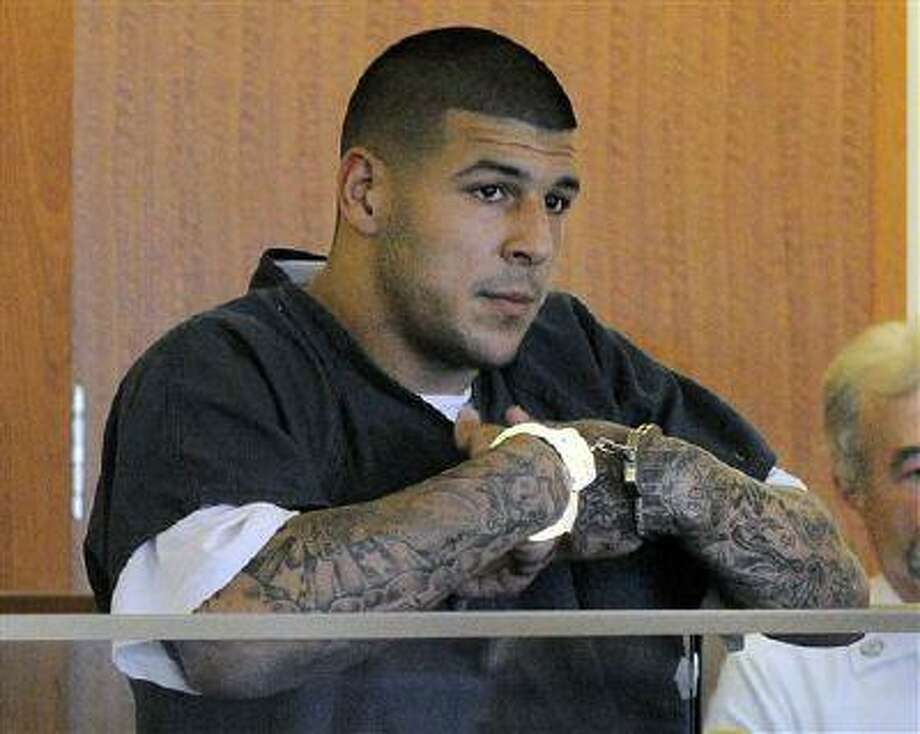 FILE - Former New England Patriots football tight end Aaron Hernandez stands during a bail hearing in Fall River Superior Court in this June 27, 2013 file photo taken in Fall River, Mass. An associate of former New England Patriots tight end Aaron Hernandez said he was told Hernandez fired the shots that resulted in the death of a semi-pro football player, according to documents filed in Florida. The records say Hernandez associate Carlos Ortiz told Massachusetts investigators that another man, Ernest Wallace, said Hernandez shot Lloyd in an industrial park near Hernandez's home in North Attleborough. (AP Photo/Boston Herald, Ted Fitzgerald, Pool) Photo: AP / Pool, Boston Herald