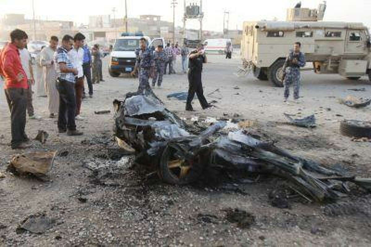 Iraqi security forces inspect the site of a car bomb attack in Kirkuk, 250 km (155 miles) north of Baghdad, July 11, 2013. Two civilians were wounded after the car bomb attack, police said. REUTERS/Ako Rasheed (IRAQ - Tags: CIVIL UNREST POLITICS)