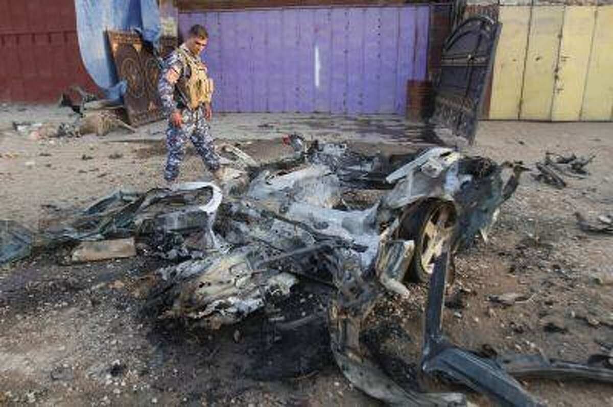 An Iraqi policeman inspects the site of a car bomb attack in Kirkuk, 250 km (155 miles) north of Baghdad, July 11, 2013. Two civilians were wounded in the car bomb attack, police said. REUTERS/Ako Rasheed (IRAQ - Tags: CIVIL UNREST POLITICS)