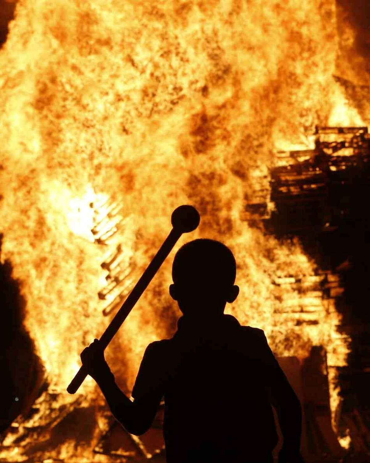 A boy watches a bonfire in the Protestant Sandy Row area of Belfast, Northern Ireland, Thursday, July 11, 2013. Hundreds of fires were set alight Thursday as loyalists celebrate The Twelfth, the holiday remembering the defeat of the Catholic King James, by the Protestant William of Orange in 1690. (AP Photo/Peter Morrison)