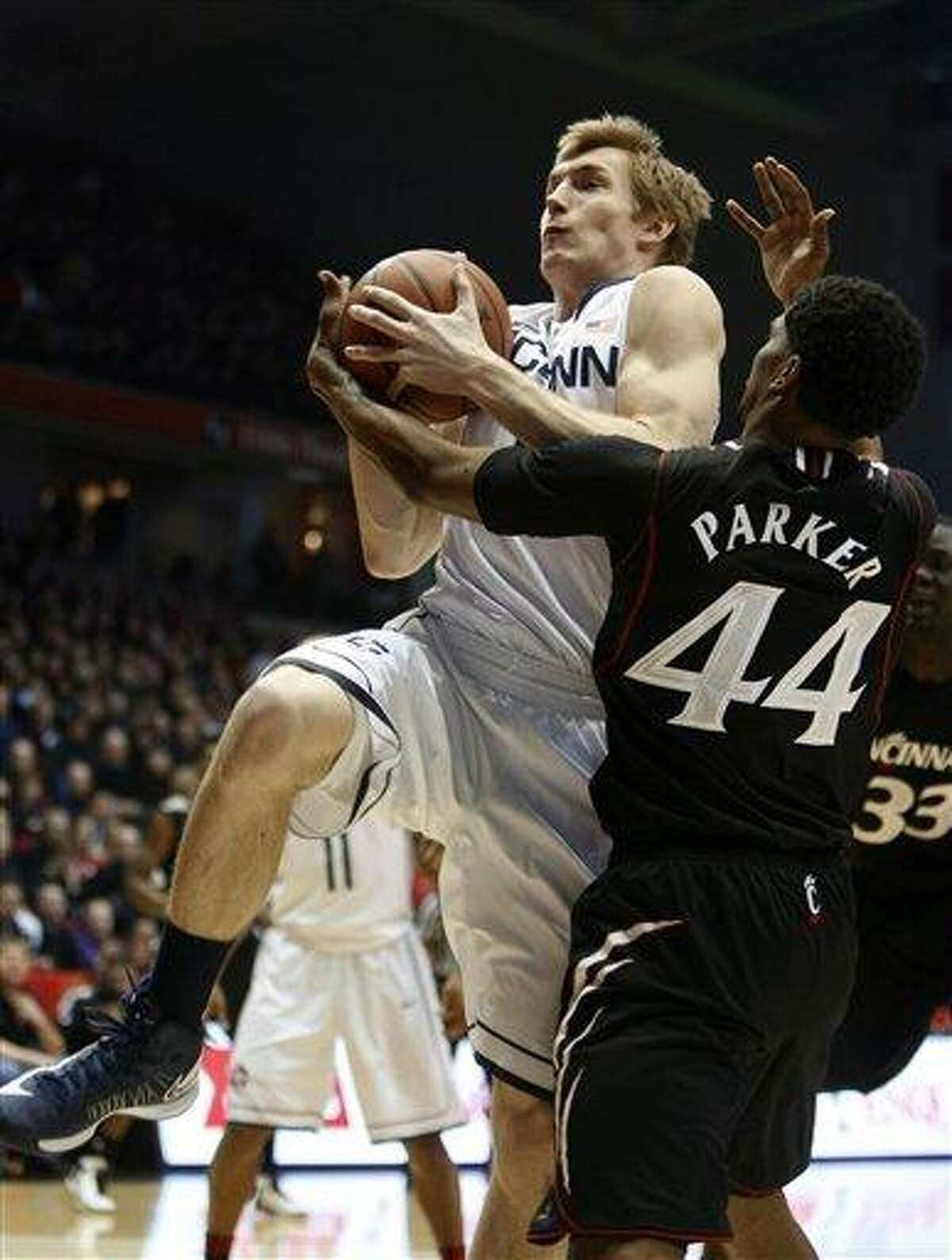 Connecticut forward Niels Giffey, left, comes down with a rebound against Cincinnati guard JaQuon Parker, right, during the first half of an NCAA college basketball game, Saturday, March 2, 2013, in Cincinnati. (AP Photo/David Kohl)