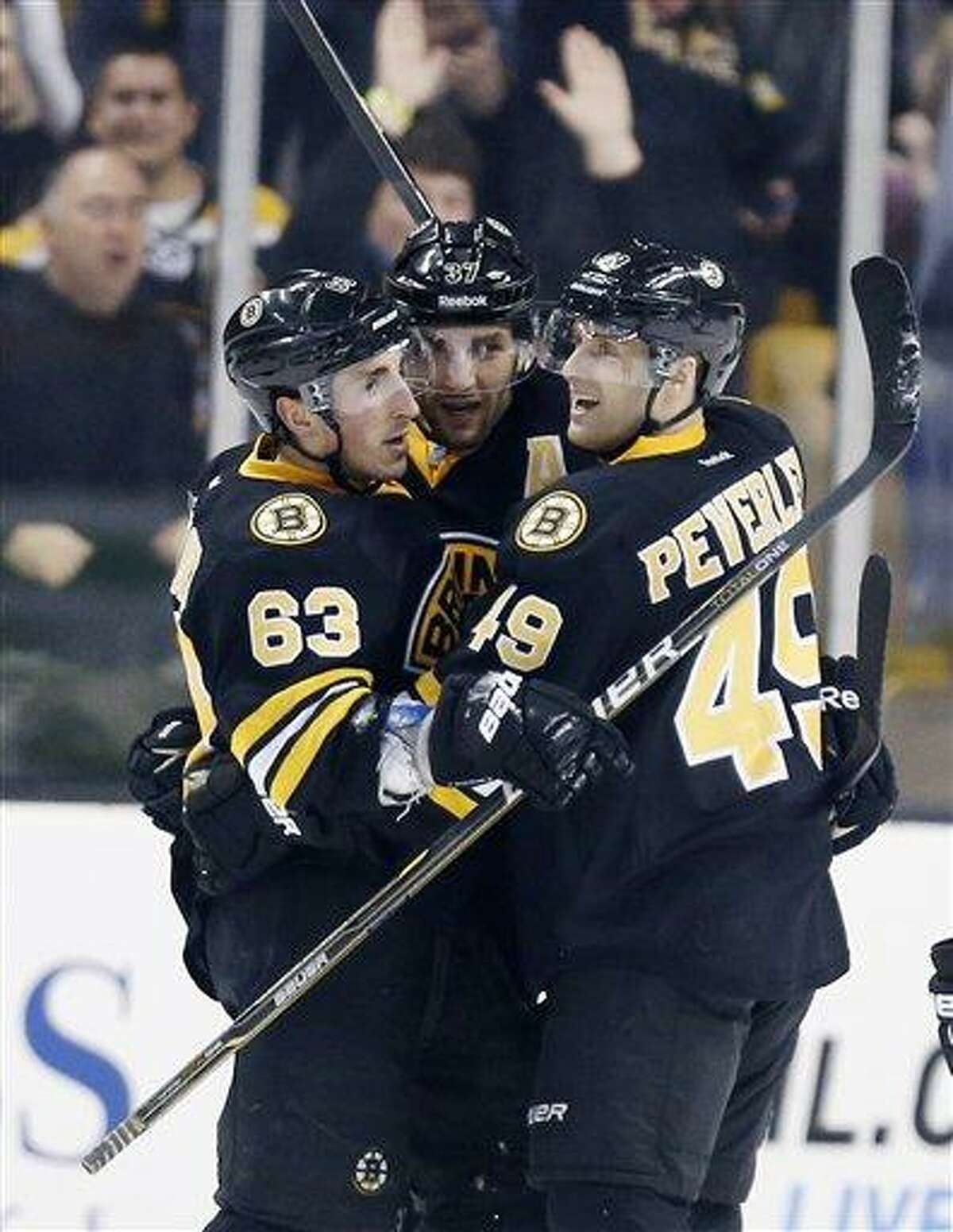 Boston Bruins' Brad Marchand (63) celebrates his go-ahead goal with teammates Patrice Bergeron (37) and Rich Peverley (49) during the third period of an NHL hockey game against the Tampa Bay Lightning in Boston, Saturday, March, 2, 2013. The Bruins won 3-2. (AP Photo/Michael Dwyer)