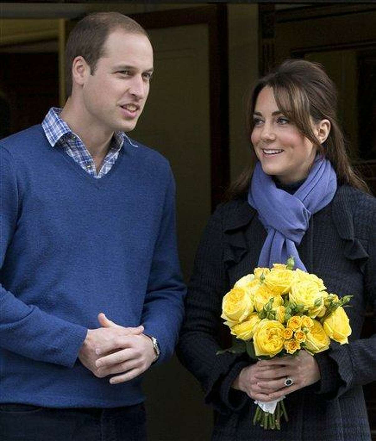Britain's Prince William stands next to his wife Kate, Duchess of Cambridge as she leaves the King Edward VII hospital in central London Thursday. AP Photo/Alastair Grant