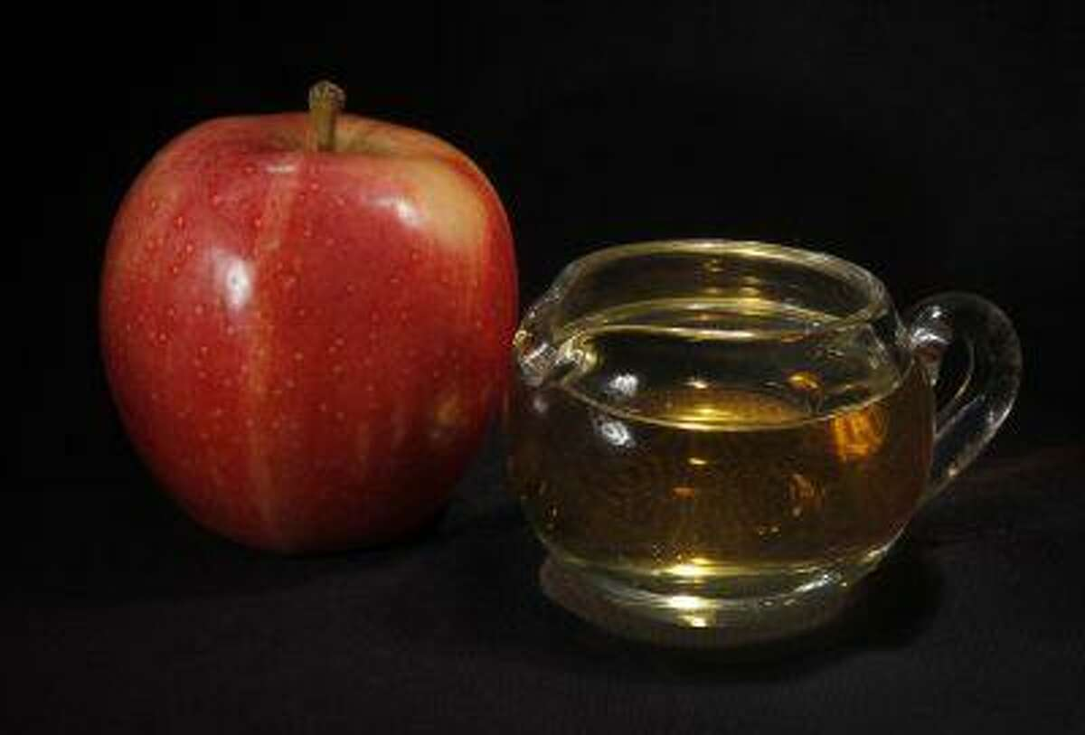 In this Sept. 15, 2011 photo, an apple and a pitcher of apple juice are posed together in Moreland Hills, Ohio. The Food and Drug Administration is setting a new limit on the level of arsenic allowed in apple juice, after more than a year of public pressure from consumer groups worried about the contaminant's effects on children. (AP Photo/Amy Sancetta, File)