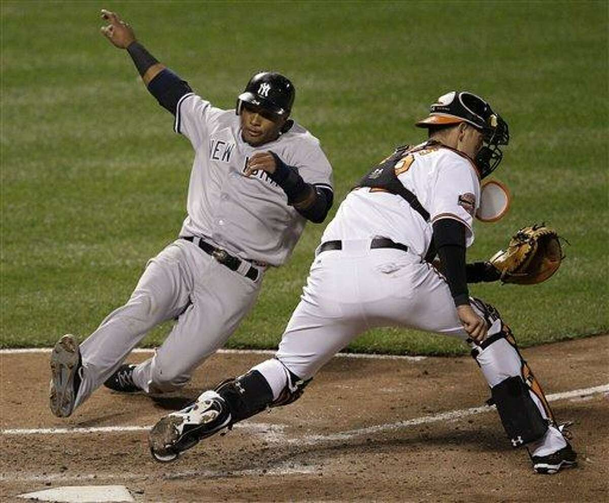 New York Yankees' Robinson Cano slides to home plate for a run past Baltimore Orioles catcher Matt Wieters on a sacrifice fly by Andruw Jones in the sixth inning of a baseball game in Baltimore, Tuesday, April 10, 2012. (AP Photo/Patrick Semansky)