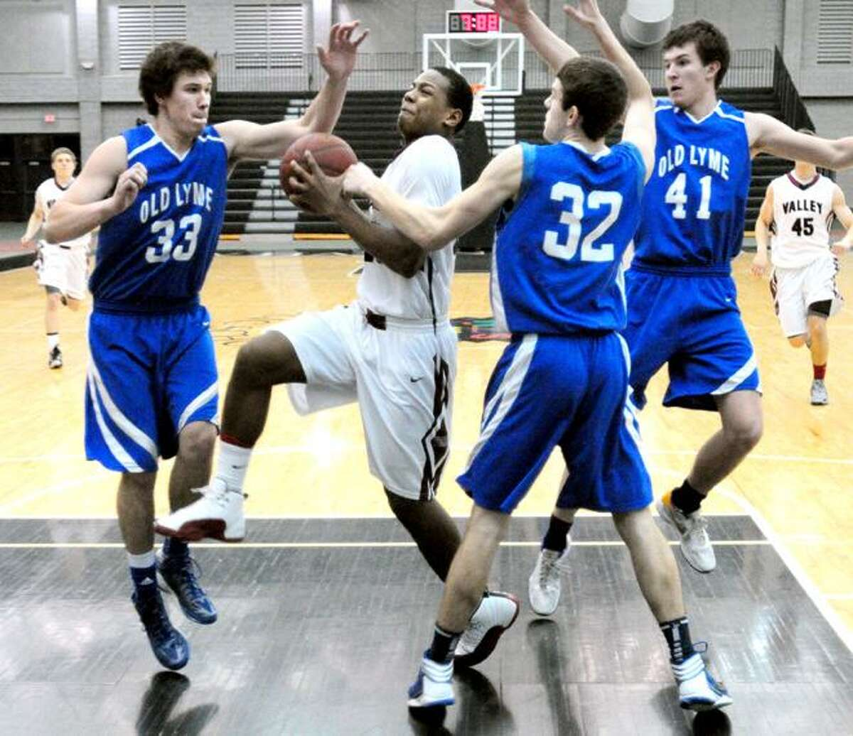 Christopher Jean-Pierre (center) of Valley Regional drives between Old Lyme players in the opening minutes of the Shoreline Conference Championship in New Haven on 3/1/2013. He was fouled on the play by Slater Gregory (left).Photo by Arnold Gold/New Haven Register
