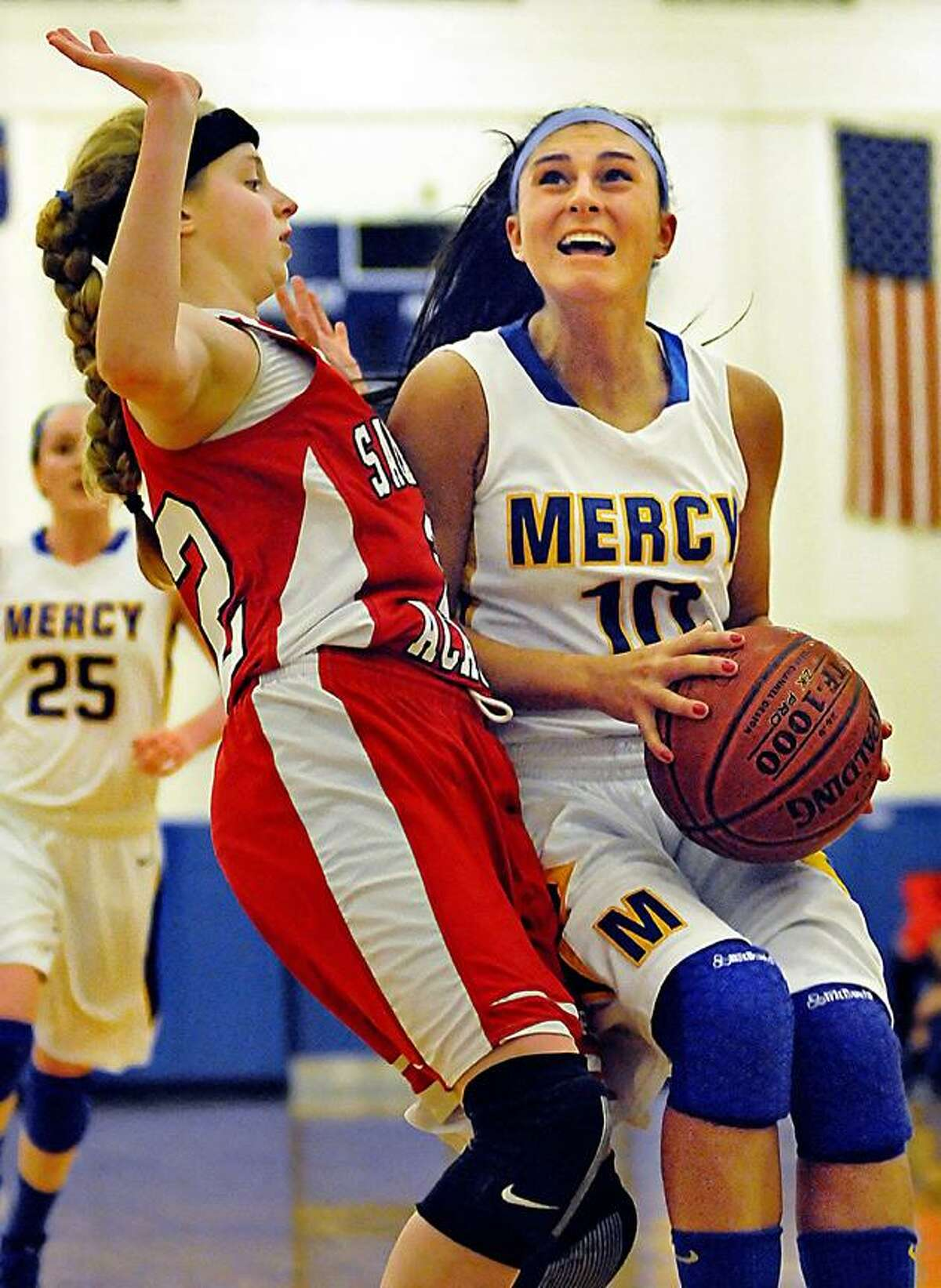 Catherine Avalone/The Middletown Press Mercy senior guard Jordyn Nappi hits the paint hard as Sacred Heart freshman Kaleigh Putnam defends Friday night during the CIAC Class LL Second Round State Tournament. The Mercy Tigers defeated the Sacred Heart Pacers 54-26.