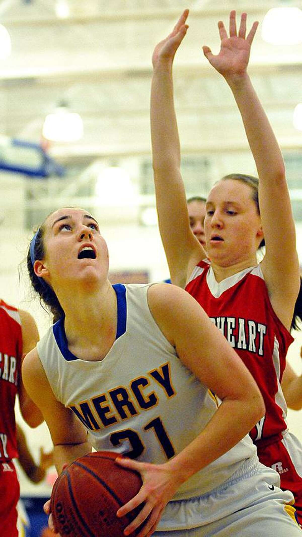 Catherine Avalone/The Middletown Press Mercy senior point guard Sheena Landy eyes the bucket as Sacred Heart freshman Kathleen Malison defends Friday night during the CIAC Class LL Second Round State Tournament. The Mercy Tigers defeated the Sacred Heart Pacers 54-26.