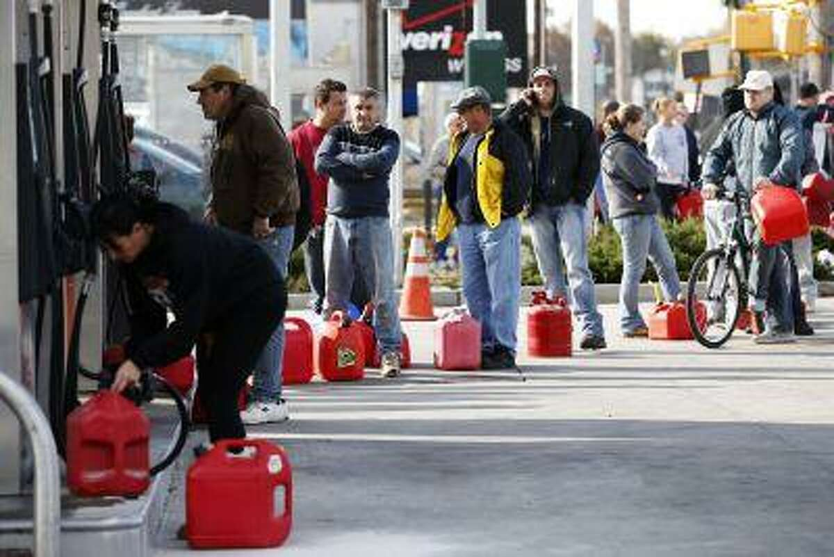 People stand in line with gas cans to fill at one of the few gas stations open on hard-hit Staten Island in New York City following Hurricane Sandy, in this Nov. 2, 2012, file photo.