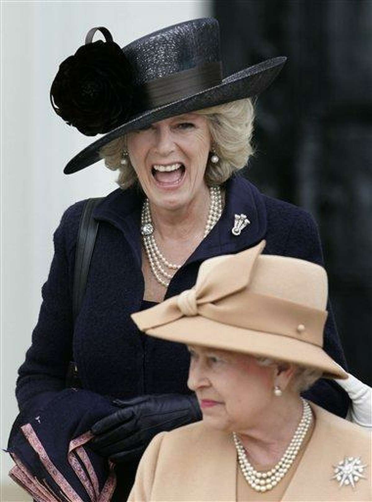 Britain's Camilla, the Duchess of Cornwall, top, laughs in 2006 as members of the royal family including Queen Elizabeth II, bottom, and Prince Philip leave after the Sovereign's Parade at the Royal Military Academy Sandhurst in England where Prince Harry, received his military commission. Queen Elizabeth II has appointed the Duchess of Cornwall the highest female rank in the Royal Victorian Order, Buckingham Palace said Monday. The announcement that Camilla has been made a Dame Grand Cross comes on the day of her seventh wedding anniversary with Prince Charles, the queen's son. Associated Press