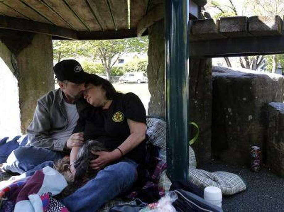 In this Wednesday, April 24, 2013 photo, Bill Neal, 41, and his partner, Diane Reedy, 42, sit beneath a play structure in Scobert Park in Eugene, Ore. The couple, have been homeless in Eugene for several months, spent the afternoon napping in the park with their dog. Earlier in the day, the Eugene City Council voted in favor of allowing the homeless to camp overnight on some city property, but not parks. (AP Photo/The Register-Guard, Paul Carter) Photo: AP / The Register-Guard