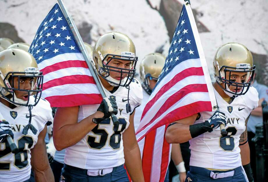 From left, Navy's Marcus Thomas (26), Evan Palelei (58) and Wave Ryder (8) head onto the field at the start of a football game against Indiana in Bloomington, Ind, on Sept. 7. The Defense Department said Tuesday that it has temporarily suspended all sports competitions at the service academies as a result of the partial government shutdown. The decision jeopardizes this weekend's football games, Air Force at Navy and Army at Boston College. Photo: Doug McSchooler -- The Associated Press  / FR170771 AP
