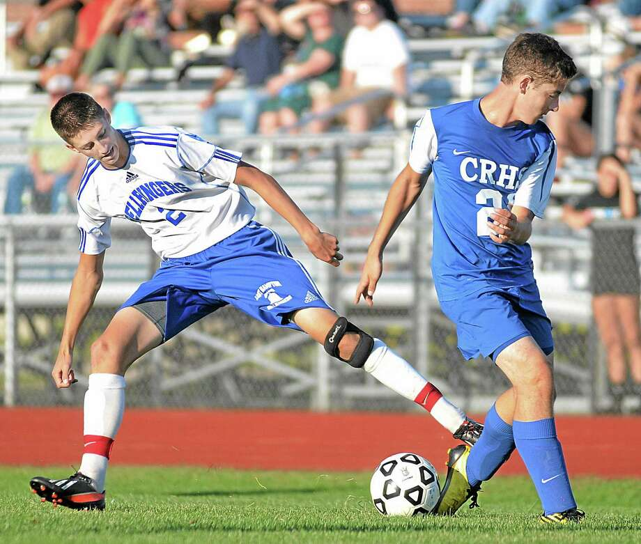 East Hampton's Connor Wall and Coginchaug's Garret D'Amato battle for control early in the second half of Tuesday afternoon's game. The Bellringers defeated the Blue Devil's 3-1 at home. Photo: Catherine Avalone — The Middletown Press  / TheMiddletownPress
