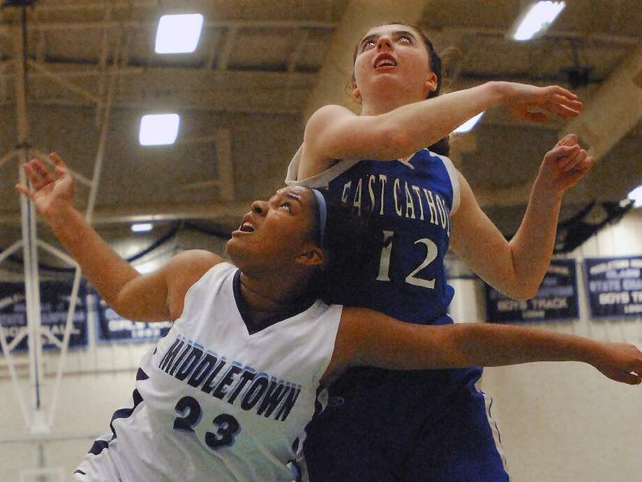 Catherine Avalone/The Middletown Press Middletown's Tamyia King is fouled by East Catholic's Liz Brasa during a fast break in the fourth quarter during the Blue Dragon season opener at home. East Catholic won 60-57.