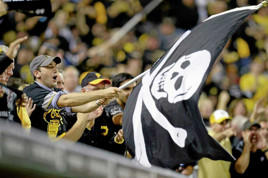 A Pittsburgh Pirates fan waves a Jolly Roger flag as the Pirates play the Cincinnati Reds in the NL wild-card playoff Tuesday in Pittsburgh. Photo: Don Wright -- The Associated Press  / FR87040 AP