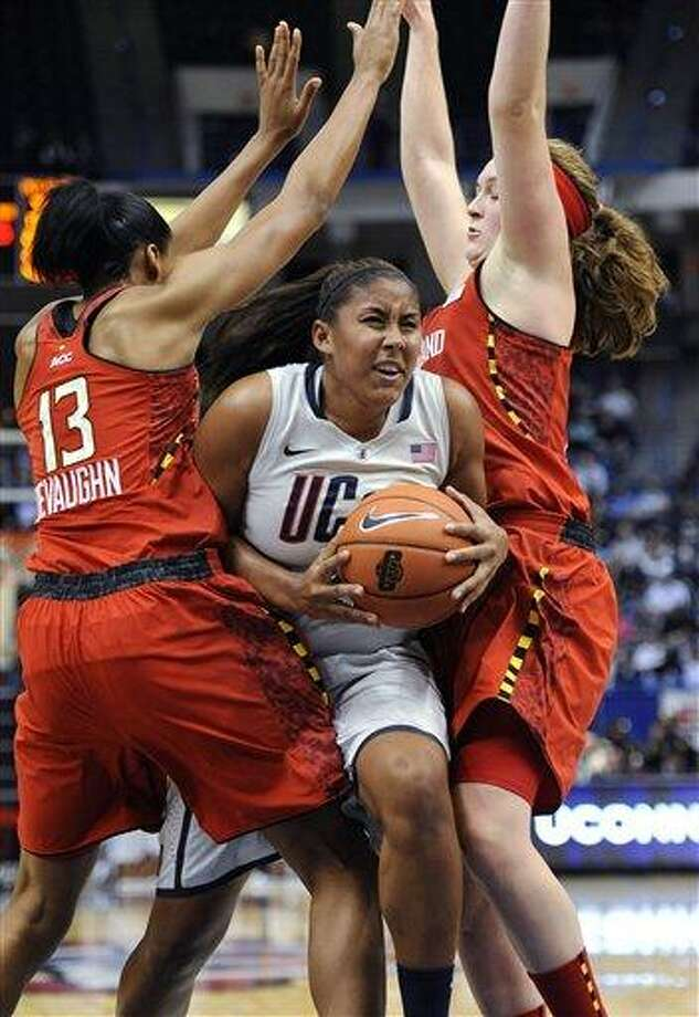 Connecticut's Kaleena Mosqueda-Lewis, center, drives to the basket between Maryland's Alicia DeVaughn, left, and Maryland's Tierney Pfirman, right, during the first half of an NCAA college basketball game in Hartford, Conn., Monday, Dec. 3, 2012. Connecticut won 63-48. (AP Photo/Jessica Hill) Photo: AP / FR125654 AP