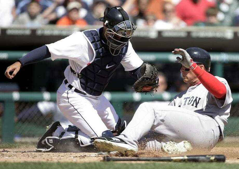 Boston Red Sox's Ryan Sweeney, right, scores past Detroit Tigers catcher Alex Avila on a sacrifice fly by Nick Punto in the third inning of a baseball game Sunday, April 8, 2012, in Detroit. (AP Photo/Duane Burleson) Photo: ASSOCIATED PRESS / AP2012