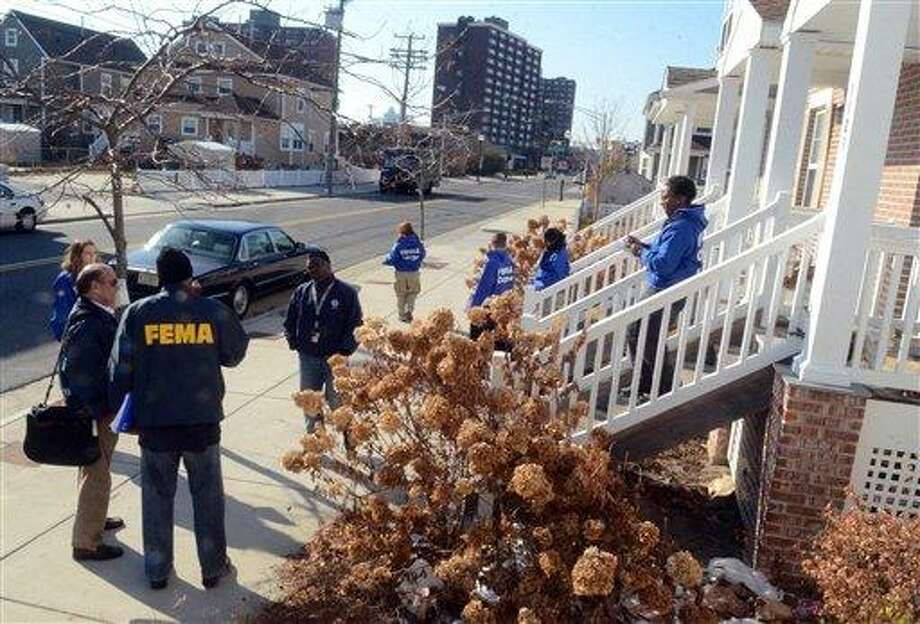 FEMA workers and FEMA Corps volunteers, canvas the Mid Town section of Atlantic City, N.J. talking with residents or leaving information in their doorway on Monday, Nov. 26, 2012. A team of college students has been working with FEMA to identify and provide services for Superstorm Sandy victims in Atlantic City. (AP Photo/Press of Atlantic City, Danny Drake) Photo: AP / The Press of Atlantic City