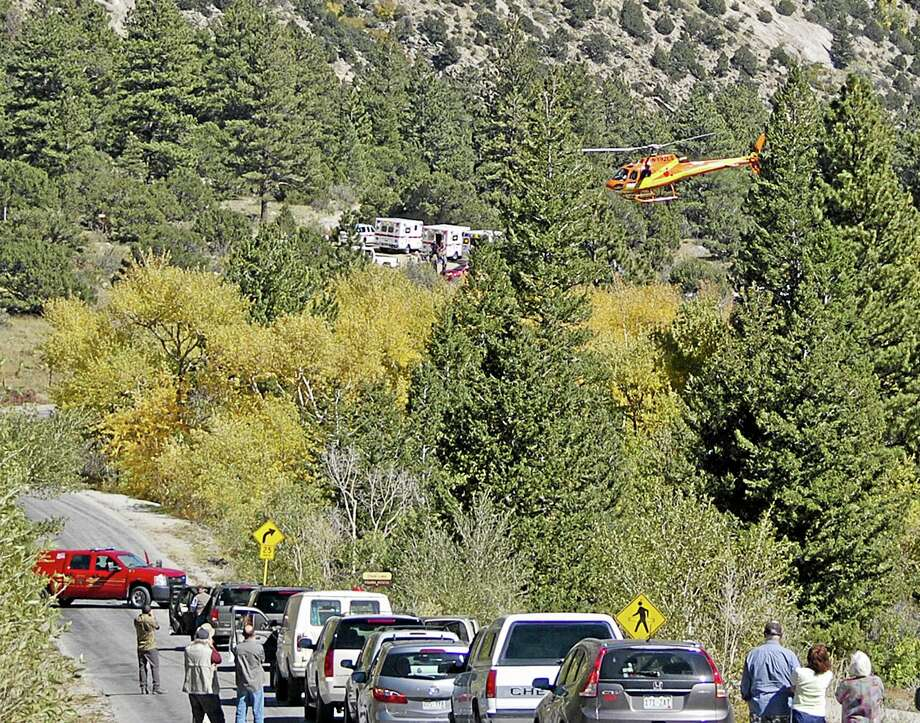 A Flight for Life Helicopter rises above backed up traffic Monday Sept. 30, 2013,  in south-central Colorado.  Roads were closed as emergency personnel work to  aid hikers trapped after a rock slide on the trail to Agnes Vaille Falls.   (AP Photo/The Mountain Mail, James Redmond) Photo: AP / The Mountain Mail