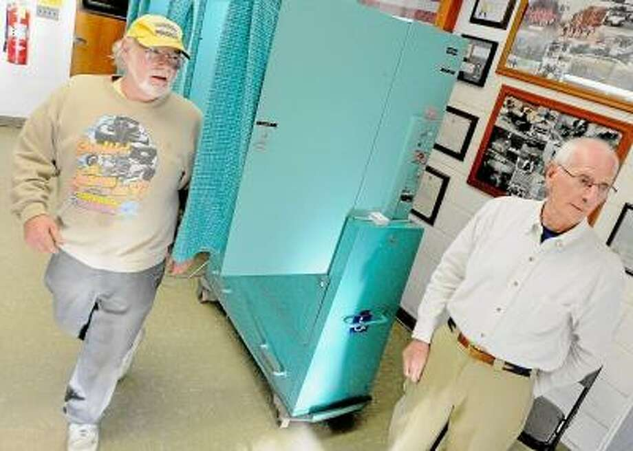 Middletown resident Joel Pear exits the voting machine Tuesday evening at South Fire District as machine tender, Frank Augeri greets neighbors as they enter the fire house. The budget for the 2013-14 fiscal year has been set at $4,605,680. Catherine Avalone/The Middletown Press / TheMiddletownPress