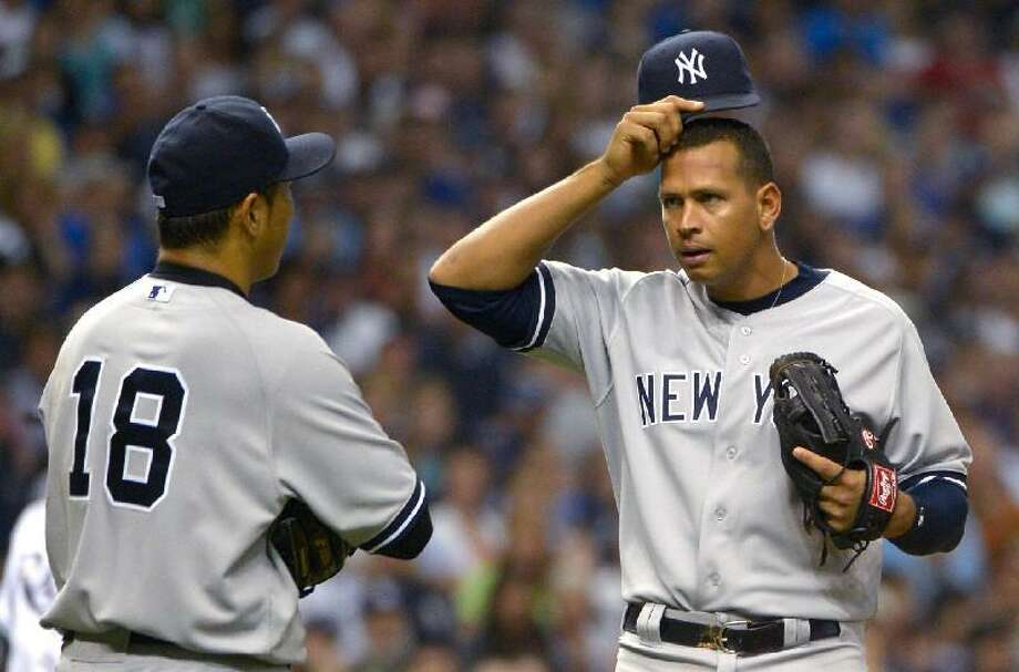 ASSOCIATED PRESS New York Yankees third baseman Alex Rodriguez, right, checks on pitcher Hiroki Kuroda after he was knocked down by a piece of broken bat from Tampa Bay Rays shortstop Reid Brignac during the sixth inning of Saturday's game in St. Petersburg, Fla. The Yankees lost 8-6.