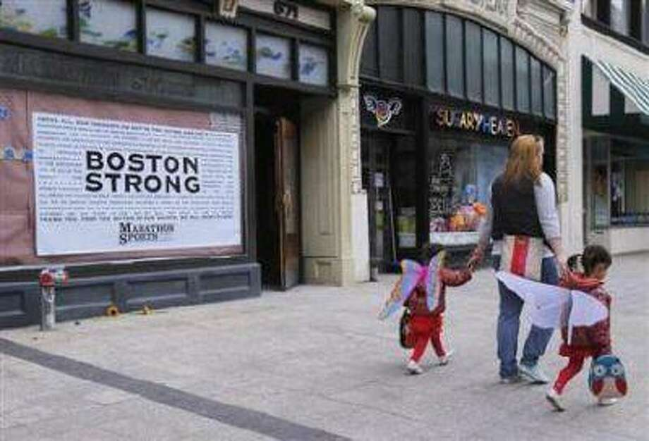 A woman walks her children wearing wings in front of the site of the first explosion on Boylston Street after the street reopened to the public since the Boston Marathon bombings in Boston, Massachusetts April 24. (Reuters/Jessica Rinaldi) / X01704