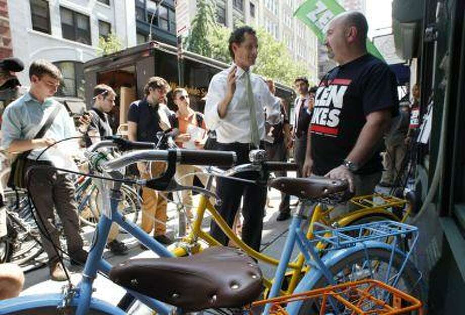 New York mayoral candidate Anthony Weiner, center, meets with John Keoshgerian, right, owner of Zen Bikes, in New York, Monday, July 8, 2013. Weiner is supporting a tax break for employers to encourage employees to bike to work. (AP Photo/Mark Lennihan) Photo: AP / AP