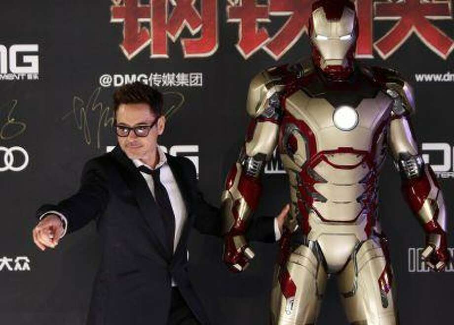 "Cast member Robert Downey Jr. poses for a photo with an Iron Man figure during a promotional event of the movie ""Iron Man 3"" before its release in China at the Imperial Ancestral Temple of Beijing's Forbidden City. Photo: REUTERS / X01757"