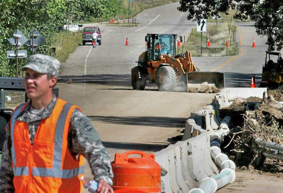 FILE - In this Sept. 20, 2013 photo, a National Guard soldier mans a roadblock as a bulldozer clears concrete flood debris from a damaged road being repaired after last week's flood, west of Longmont, Colo. A bitter budget fight has led to a U.S. government shutdown Tuesday, Oct. 1, 2013, leaving hundreds of thousands of federal workers without paychecks and shutting down federal services all over the country. National Guard soldiers rebuilding washed-out roads in Colorado would apparently be paid on time _ along with the rest of the country's active-duty personnel _ under a bill passed hours before the shutdown. (AP Photo/Brennan Linsley, File) Photo: AP / AP