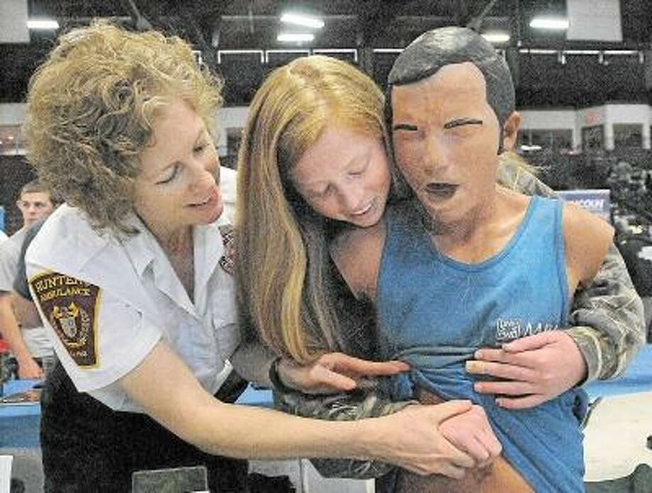 Catherine Avalone/The Middletown Press Sheri Sawallich, an EMT at Hunter's Ambulance teaches the Heimlich maneuver to Coginchaug sophomore Michelle Hargreaves, 16, at the Annual Career Expo sponsored by the Middlesex Chamber of Commerce and the Middlesex School Consortium Thursday morning at the Spurrier-Snyder Rink at Wesleyan University. / TheMiddletownPress
