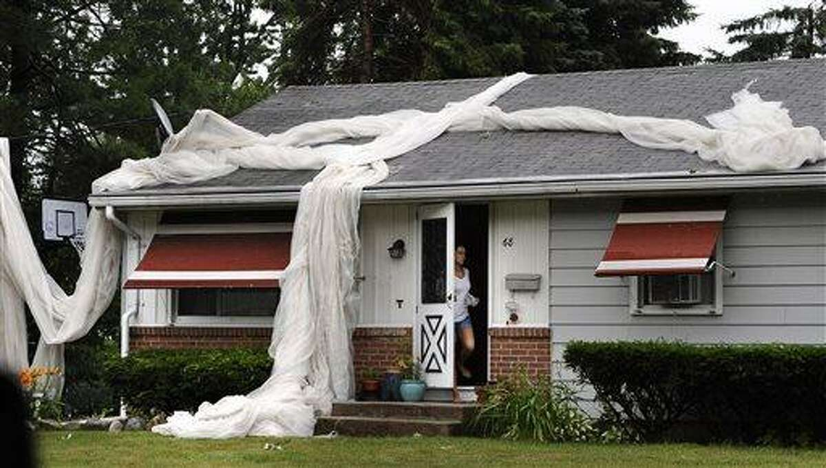 Tobacco netting is seen on top of a home in a neighborhood in Windsor Locks after a powerful storm, possibly producing a tornado, tore through the towns of Windsor Locks and East Windsor, Conn., Monday, July 1, 2013. (AP Photo/Journal Inquirer, Jessica Hill) MANDATORY CREDIT