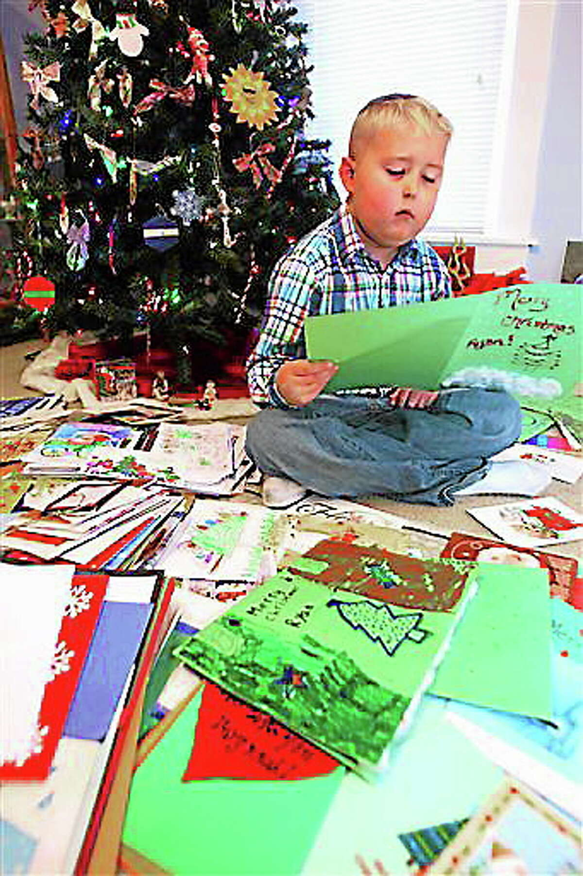 In this Nov. 8, 2013 photo, Ryan Beining, 8, reads Christmas cards from all over the world is his house in Kokomo, Ind. Ryan Beining's teachers didn't know what to do when they found out the 8-year-old's cancer treatments had stopped working. Ryan's family found out Oct. 1 that his treatments were no longer slowing the growth of his aggressive brain tumor. But an effort to send the boy Christmas cards has taken off, resulting in 6,000 greetings from around the world. (AP Photo/The Kokomo Tribune, Tim Bath)