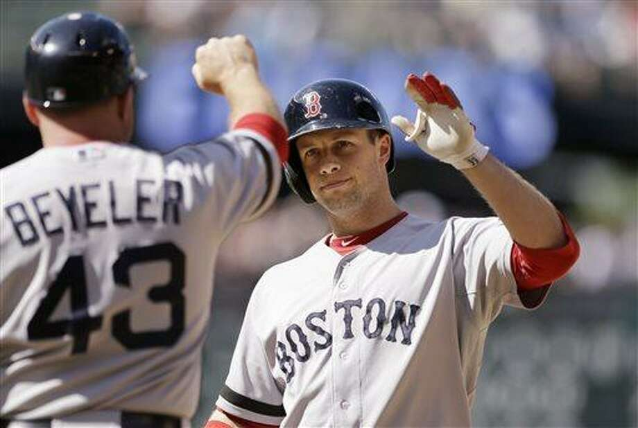 Boston Red Sox's Daniel Nava, right, is congratulated by first base coach Arnie Beyeler after hitting an RBI-single against the Seattle Mariners in the 10th inning of a baseball game on Thursday, July 11, 2013, in Seattle. The Red Sox won in 10 innings 8-7. (AP Photo/Elaine Thompson) Photo: AP / AP
