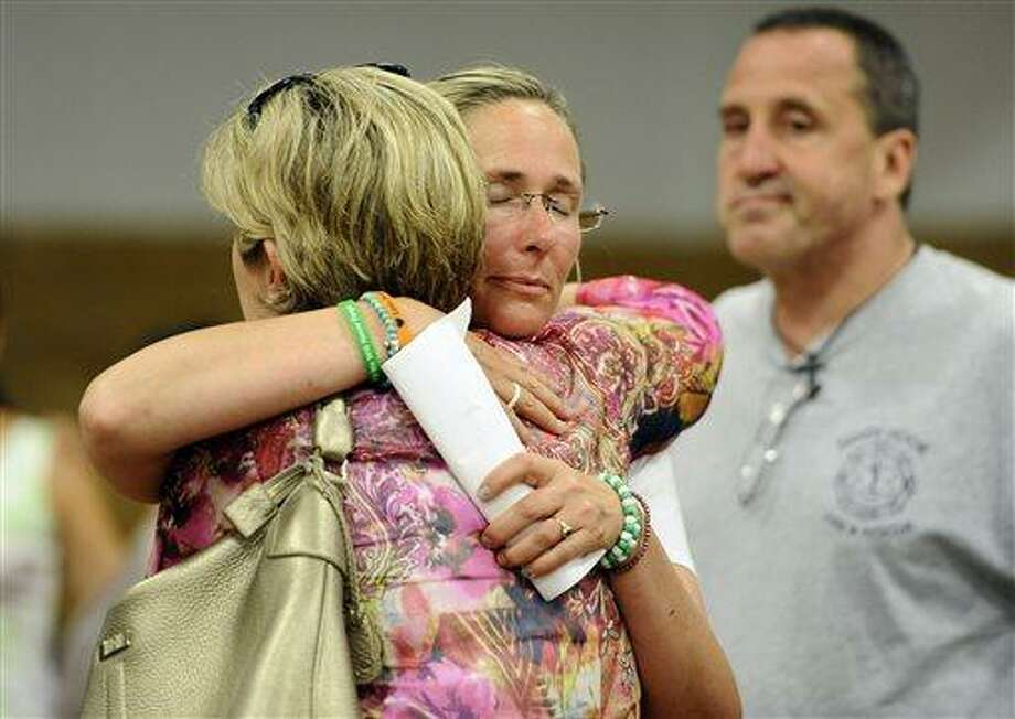 Scarlett Lewis, mother of Sandy Hook Elementary School shooting victim Jesse Lewis, center, hugs Lynn McDonnell, mother, of victim Grace McDonnell, left,  as Neil Heslin, father of victim Jesse Lewis, right, looks on after a public forum on the distribution of Newtown donations at Edmond Town Hall in Newtown, Conn., Thursday, July 11, 2013.  A community foundation has been tasked with dividing up $11.4 million that was raised with the help of the United Way. At Thursday's meeting, people can comment on the disbursement of $7.7 million that has been set aside for the families of the 26 people who were killed, two wounded teachers and the families of 12 children who escaped. (AP Photo/Jessica Hill) Photo: AP / FR125654 AP