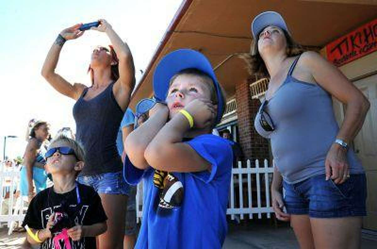 In this Oct. 21, 2012, file photo Lucas LaPointe, 6, center, covers his ears at the Jacksonville Sea and Sky Spectacular in Jacksonville Beach, Fla. (AP Photo/Florida Times-Union, Bruce Lipsky, File)
