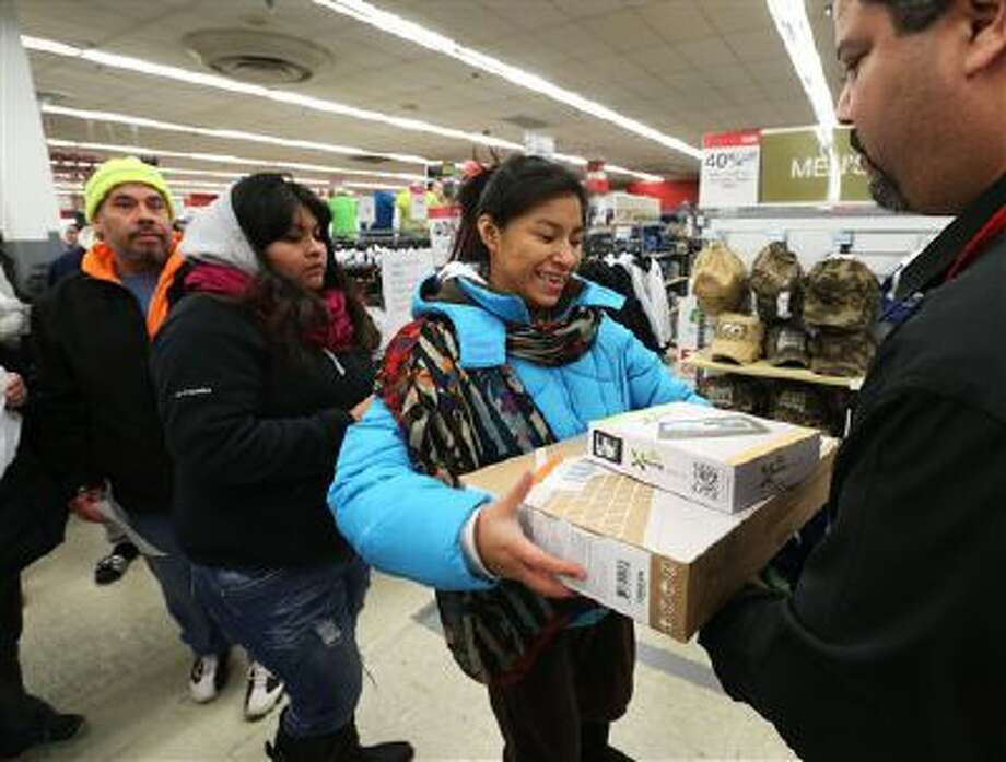 Rosa Rodriguez, of Chicago, picks up a tablet and a laptop during the doorbuster deals at the Kmart store on Addison St., on Thursday, Nov. 28, 2013 in Chicago, Ill. Photo: AP Images For Kmart / AP Images