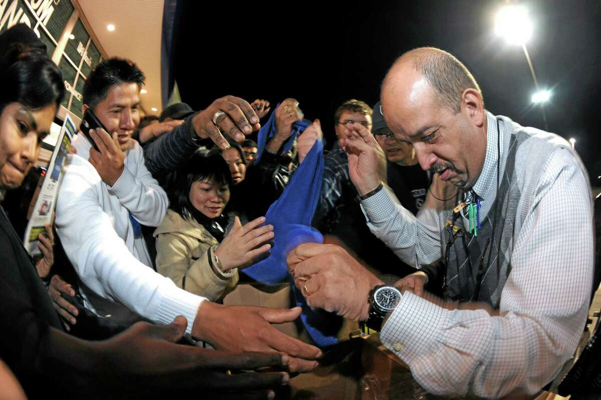 Best Buy bargain hunters swarm manager Ramon Estevez, right, as he hands out scarves and hats that will identify those eligible for specially priced door-buster sale items late in the evening on Thanksgiving Day, Thursday, Nov. 28, 2013, in Dunwoody, Ga. Instead of waiting for Black Friday, which is typically the year's biggest shopping day, more than a dozen major retailers opened on Thanksgiving this year. (AP Photo/David Tulis)